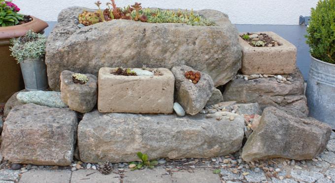Steinegarten mit Pflanztrögen vormHaus